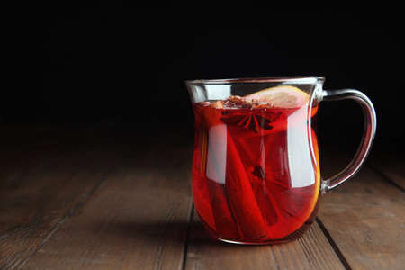 Cup with red mulled wine on wooden table against dark background. Space for text