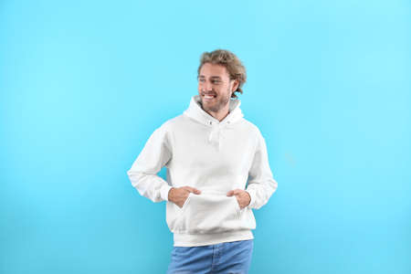 Portrait of man in hoodie sweater on color background. Space for design