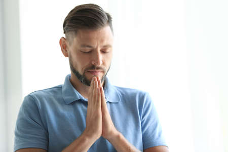 Man with hands clasped together for prayer on light background. Space for text Stock Photo