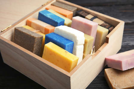 Many different handmade soap bars in wooden box on table, closeup 免版税图像