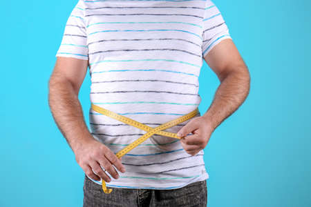 Fat man with measuring tape on color background, closeup. Weight loss Stock Photo