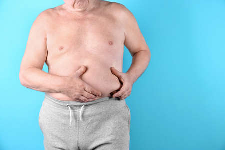 Fat senior man on color background, space for text. Weight loss