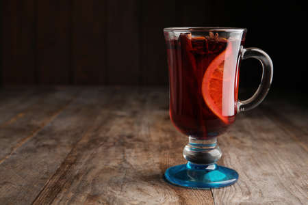 Glass with red mulled wine on wooden table. Space for text
