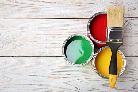 Boîtes de peinture et pinceau sur fond de bois, vue de dessus. Espace pour le texte
