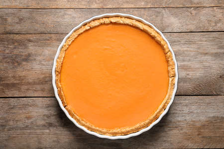 Fresh delicious homemade pumpkin pie on wooden background, top view