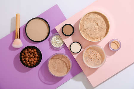 Flat lay composition with various makeup face powders on color background