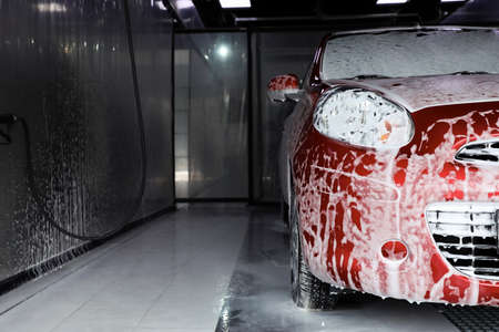Auto covered with foam at car wash, closeup. Space for text