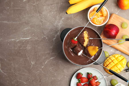 Flat lay composition with chocolate fondue in pot, fruits and space for text on gray background