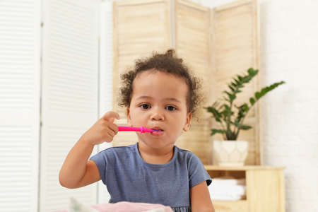 Cute African-American girl with toothbrush on blurred background