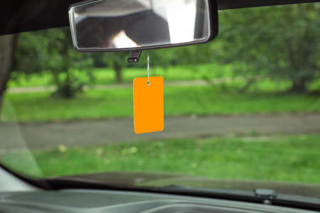 Air freshener hanging in car against windshield