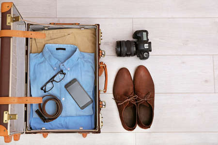 Packed suitcase on wooden background, top view. Space for text
