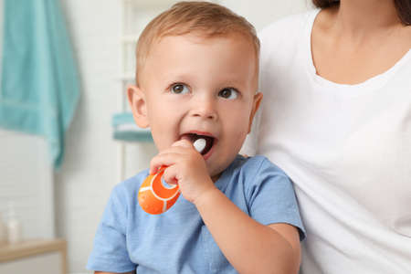 Woman and her son with toothbrush on blurred background 版權商用圖片