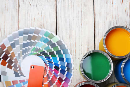 Cans with paint and color palette on wooden background, top view Stock Photo