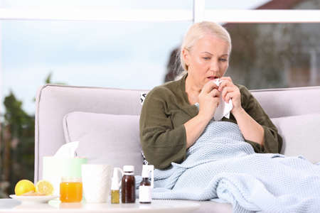 Ill mature woman suffering from cough at home. Space for text