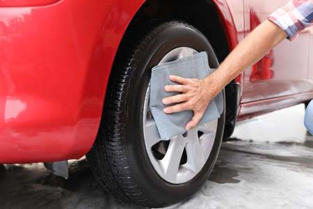 Man cleaning automobile wheel with duster, closeup. Car wash service 版權商用圖片