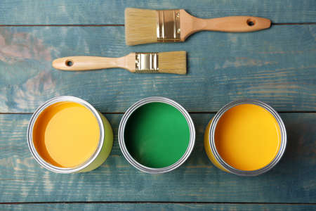 Cans with paint and brushes on wooden background, top view