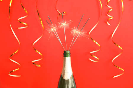 Creative composition with bottle of champagne and sparklers on color background