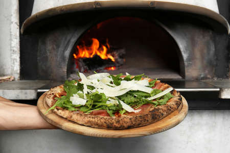 Professional chef holding tasty Italian pizza near oven in restaurant, closeup 写真素材