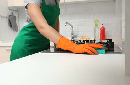 Woman cleaning gas stove with sponge in kitchen Stock fotó
