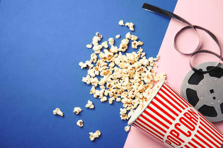 Tasty popcorn and film reel on color background, top view with space for text. Cinema snack Stockfoto