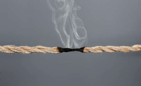 Rope burnt to breaking point on dark background Stock Photo
