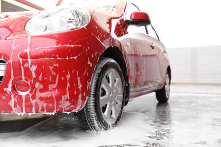 Red auto with foam at car wash. Cleaning service Фото со стока