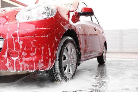 Rotes Auto mit Schaum bei Autowaschanlage. Reinigungsservice