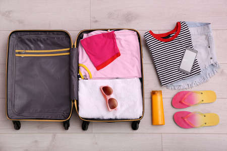 Packed suitcase on wooden background, top view