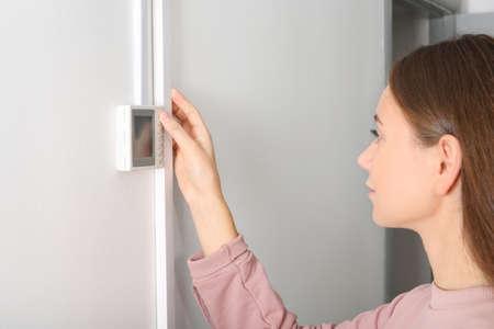 Mujer ajustando el termostato en la pared blanca. Sistema de calefacción