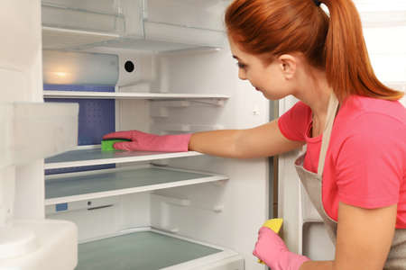Woman in protective gloves cleaning refrigerator with sponge indoors