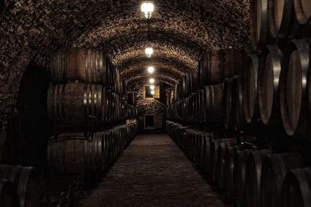 Barriles de madera con whisky en bodega oscura Foto de archivo
