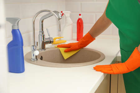 Woman in protective gloves cleaning kitchen sink with rag, closeup