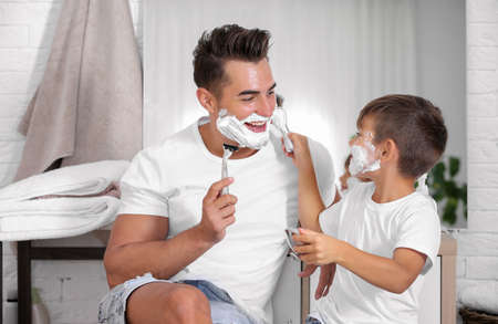 Father and son having fun while shaving in bathroom Stock Photo