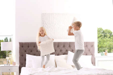 Happy children having pillow fight on bed at home Stock fotó