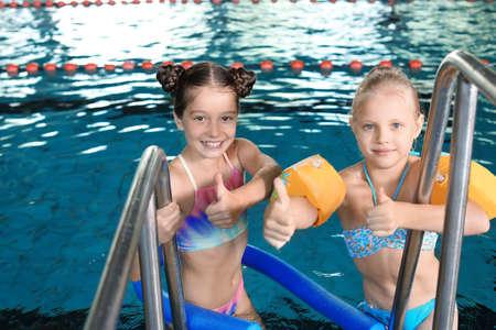 Cute little girls in indoor swimming pool Archivio Fotografico