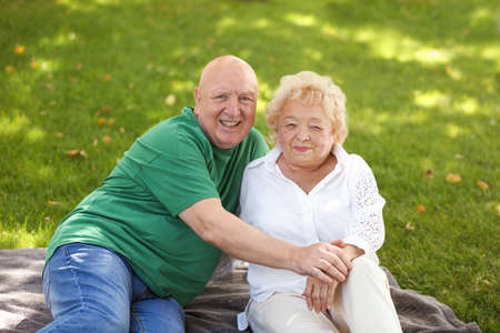 Happy elderly couple in park on sunny day Stock Photo