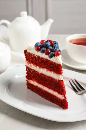 Plate with piece of delicious homemade red velvet cake on table