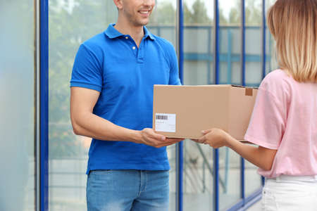Young woman receiving parcel from courier outdoors. Delivery service