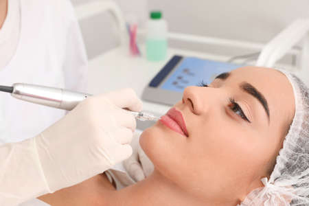 Young woman undergoing procedure of permanent lip makeup in tattoo salon, closeup Standard-Bild