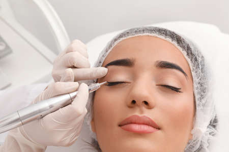 Young woman undergoing procedure of permanent eye makeup in tattoo salon, closeup Stock Photo