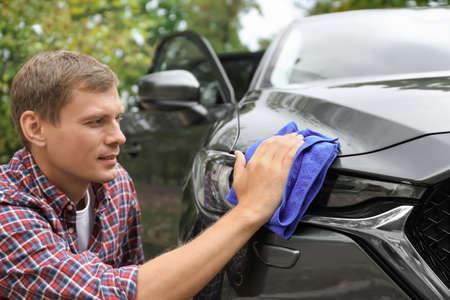 Man washing car headlight with rag outdoors Stock Photo