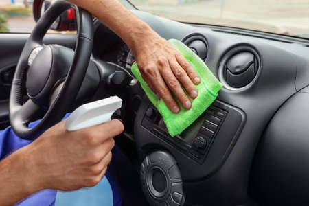 Man cleaning automobile dashboard with duster and detergent, closeup. Car wash service