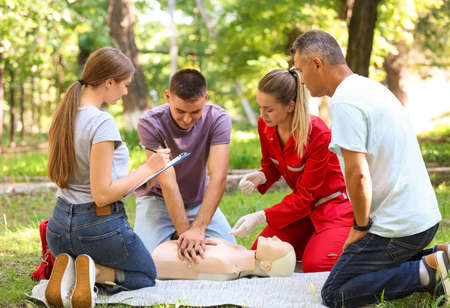 Group of people having first aid class with mannequin outdoors Banco de Imagens