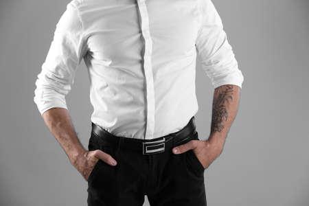 Tattooed man on grey background, closeup view Archivio Fotografico