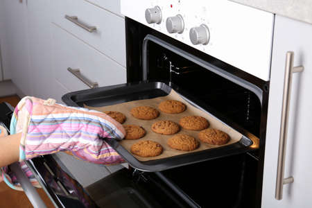 Woman taking baking tray with delicious cookies out of electric oven in kitchen, closeup Reklamní fotografie