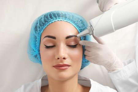 Woman undergoing laser tattoo removal procedure in salon, closeup