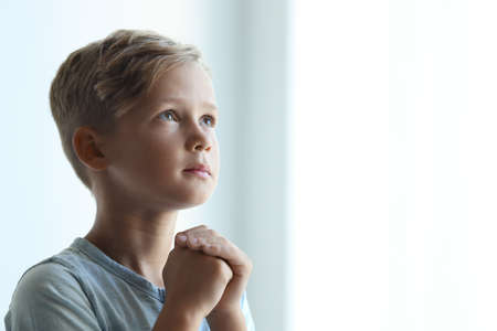 Little boy with hands clasped together for prayer on light background. Space for text Stock fotó