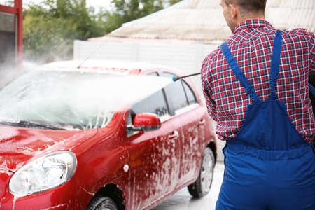 Trabajador masculino limpieza de vehículos con chorro de agua a alta presión en el lavado de autos Foto de archivo