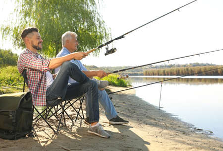 Father and adult son fishing together from riverside on sunny day Stok Fotoğraf
