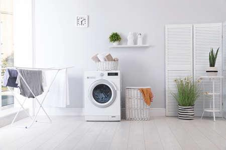 Interior de la sala de lavandería con lavadora junto a la pared Foto de archivo